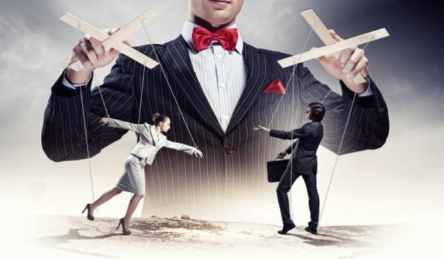 Puppeteer controlling two businesspeople