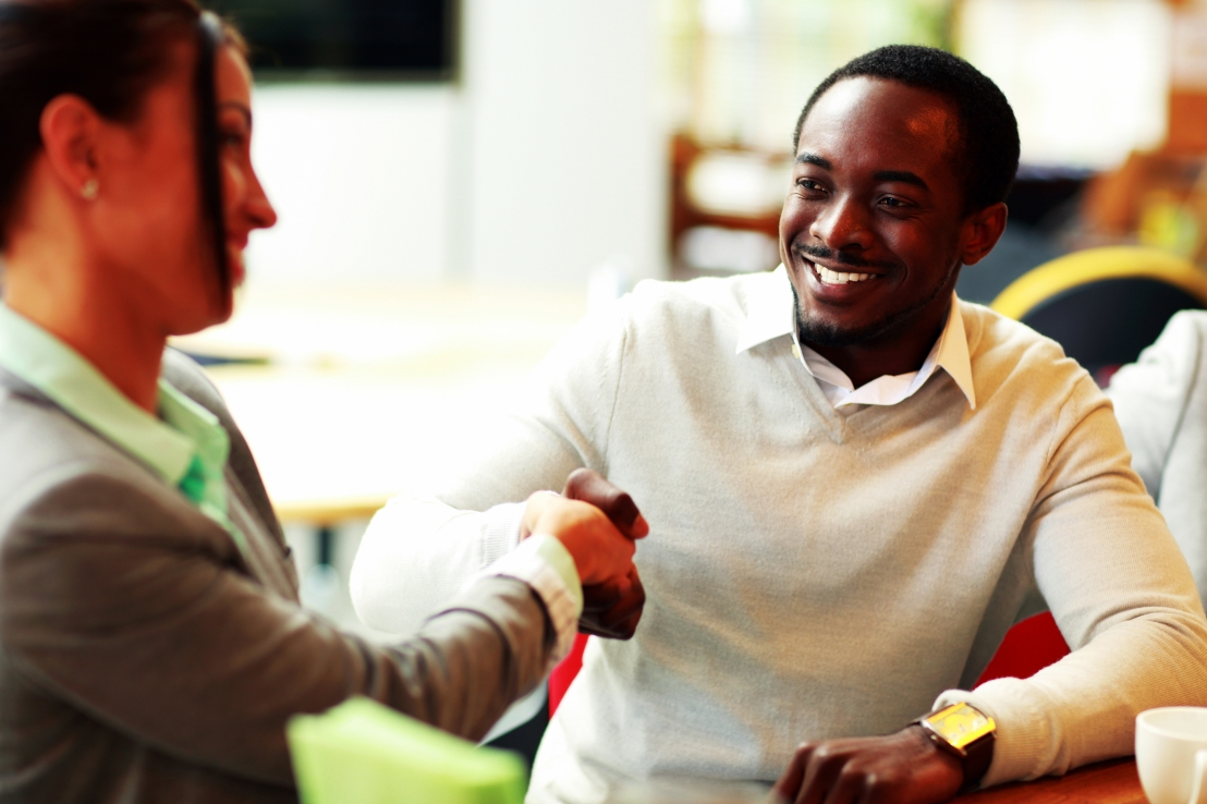 Woman and man shaking hands in a coffee shop